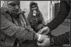 Centre de tri et d'enregistrement «Paul-Hallen», Passau, Allemagne. En arrivant dans cette petite ville frontalière avec l'Autriche, les réfugiés touchent pratiquement au but. C'est là qu'ils vont enfin pouvoir faire leur demande d'asile pour rester en Europe, comme Ola et Hla, deux étudiantes syriennes. Auparavant, ils subissent quelques derniers contrôles: fouille au corps, relevé d'empreintes digitales, etc...