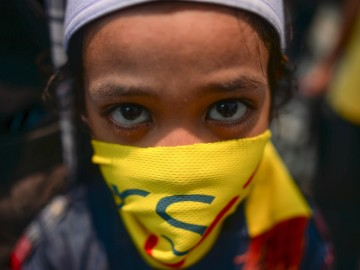 A child using a banner to cover his face looks on as Maria Chin Abdullah (not pictured), chairperson of Bersih -- the coalition of Malaysian NGOs and activist groups -- speaks to journalists after giving statements on the groups that staged the huge August 29 rally, at police headquarters in Kuala Lumpur on September 2, 2015. The organisers of the massive weekend demonstration demanding the Malaysian prime minister's removal over corruption allegations were summoned by police on September, after the government earlier threatened they could face charges. Meanwhile, police said on September 3 that former Malaysian premier Mahathir Mohamad would also be questioned over statements he made at the demonstrations.      AFP PHOTO / MOHD RASFAN        (Photo credit should read MOHD RASFAN/AFP/Getty Images)